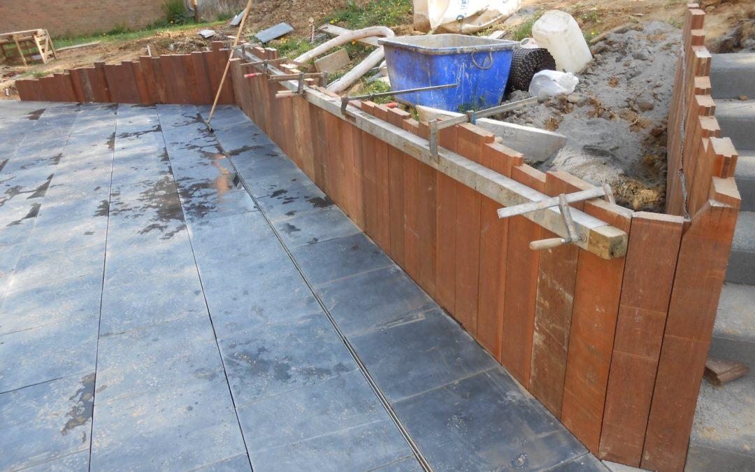 Réalisation d'une terrasse en pierre de taille 60/60 avec un muret de soutien en bois exotique